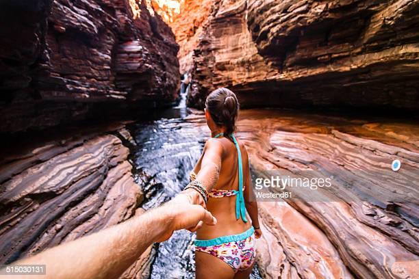 Australia, Western Australia, Karijini National Park, Hancock Gorge, couple holding hands while walking through canyon, partial view