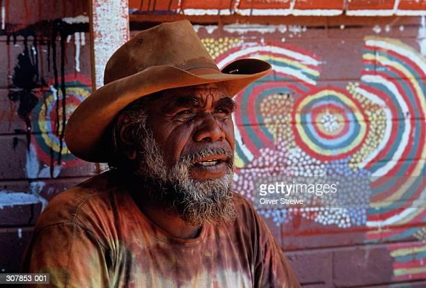 Australia,Aboriginal man in hat,Aboriginal art on wall behind