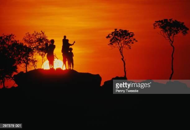 Australia,Arnhem Land,Dippirringur, silhouette of family on rock,sunse