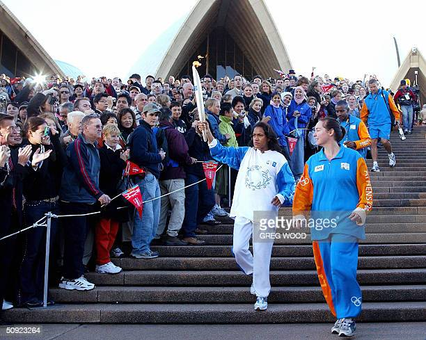 Australian 400metre Sydney Olympic track gold medallist Cathy Freeman holds the Olympic flame as she leaves the Sydney Opera House 04 June 2004 The...