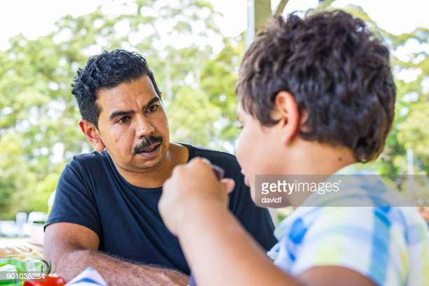 australian aboriginal man and boy talking - genderblend stock pictures, royalty-free photos & images