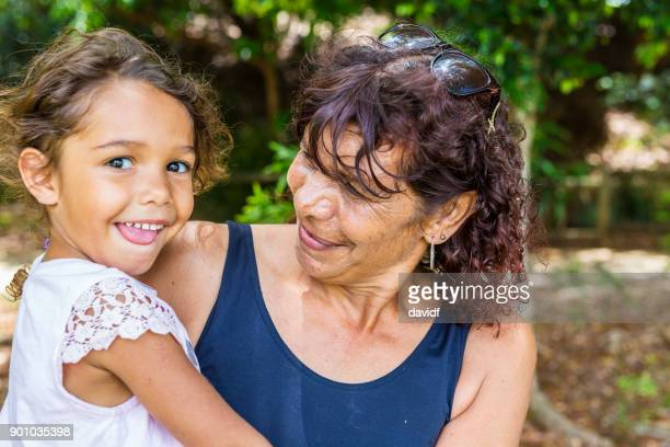 australian aboriginal woman hugging her grandaughter - australian culture stock pictures, royalty-free photos & images