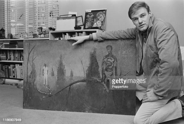Australian actor and painter Keith Michell pictured in his studio with one of his paintings in London in March 1965