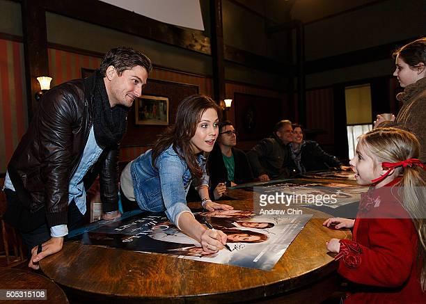 Australian actor Daniel Lissing and American actress Erin Krakow autographs for an American fan Tessa Watchous from Kansas during Hearties Family...
