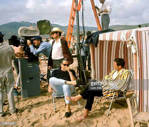 Australian actor George Lazenby sitting on a beach with producer Albert R Broccoli during the filming of the James Bond film 'On Her Majesty's Secret...