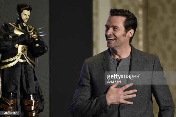 Australian actor Hugh Jackman admires a Wolverine puppet gift during a press conference for the film 'Logan' in Taipei on February 28 2017 Jackman...