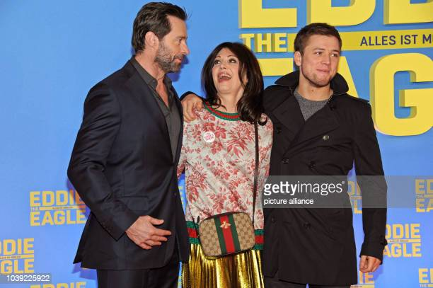 Australian actor Hugh Jackman and Welsh actor Taron Egerton pose with German actor Iris Berben as they arrive for a special screening of 'Eddie The...