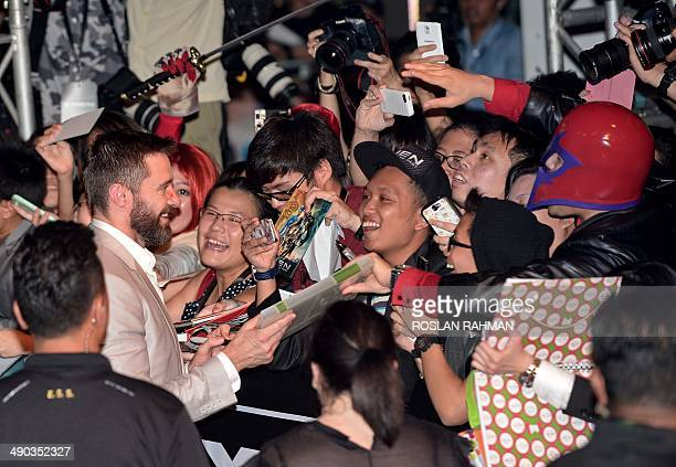 Australian actor Hugh Jackman greets the fans upon his arrival on the blue carpet in Singapore on May 14, 2014. The three actors from X-Men: Days Of...