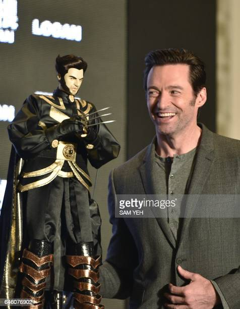 Australian actor Hugh Jackman looks at a gift of a Wolverine puppet during a press conference for the film 'Logan' in Taipei on February 28 2017...