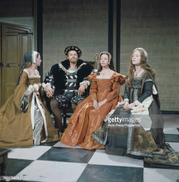 Australian actor Keith Michell pictured dressed in period costume as King Henry VIII with three of his six wives during production of the BBC TV...