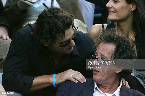 Australian actors Eric Bana and Geoffrey Rush hold a conversation before the start of the Men's Final during day fourteen of the Australian Open...