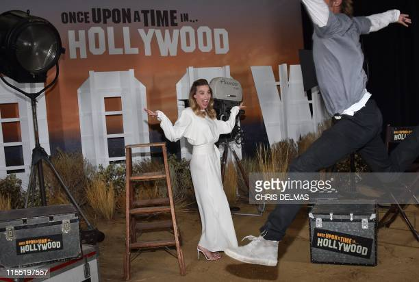 "Australian actress Margot Robbie laughs as US actor Brad Pitt tries to photobomb her during the photo call for Sony Pictures' ""Once Upon a Time in..."