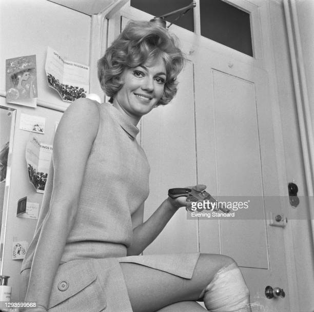 Australian actress Veronica Lang with a prop gun and a bandaged knee, UK, May 1967.