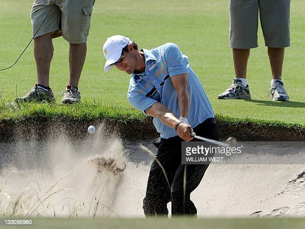 Australian Adam Scott chips out of a bunker as he and South Korea's KJ Choi defeat Tiger Woods and KJ Choi of the US during their President's Cup...