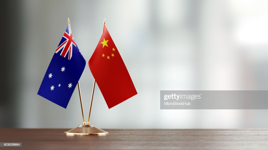Australian And Chinese Flag Pair On A Desk Over Defocused Background : Stock Photo