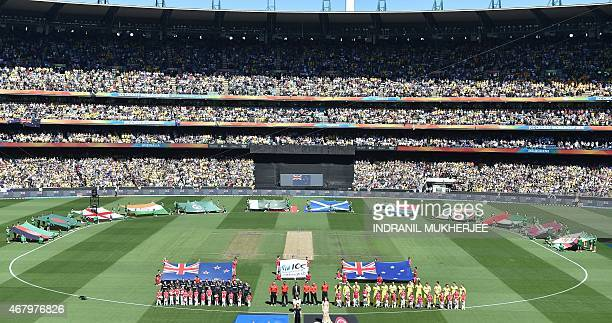 Australian and New Zealand cricketers stand for the national anthem during the 2015 Cricket World Cup final between Australia and New Zealand in...