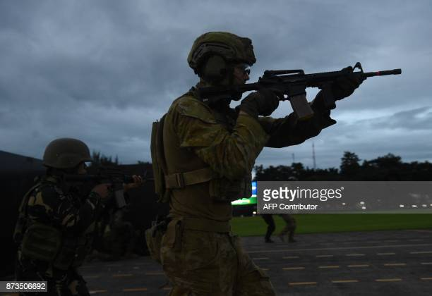 Australian and Philippine soldiers simulate an antiterrorism drill during a visit by Australian Prime Minister Malcolm Turnbull to the military...