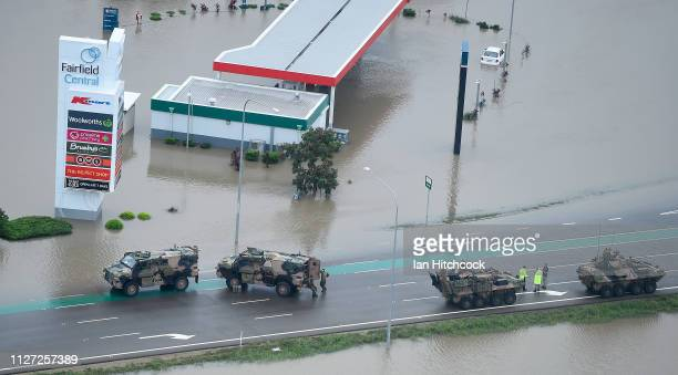 Australian army armoured vehicles can be seen on a flooded road in the Townsville suburb of Idalia on February 04 2019 in Townsville Australia...