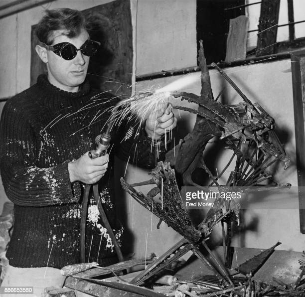 Australian artist Donald Brook works on his sculpture 'Jester in Machinery' with a welding kit at Digswell House Hertfordshire UK 27th January 1961