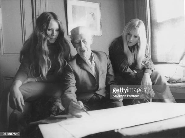 Australian artist Norman Lindsay demonstrates his skills to two young art students September 1969