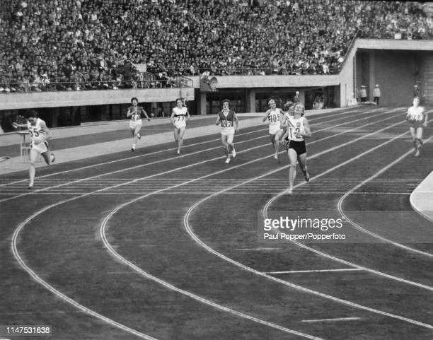 Australian athlete Betty Cuthbert finishes in first place to win the gold medal for Australia ahead of Ann Packer of Great Britain in the final of...