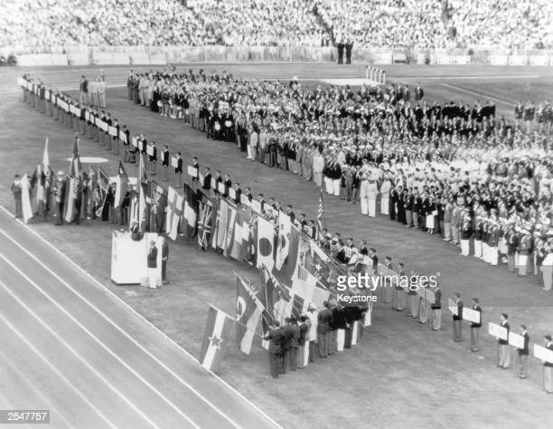 Australian athlete John Landy stands at the podium and takes the Olympic oath while athletes from competing nations hold their national flags during...