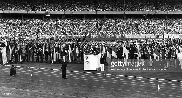 Australian athlete John Landy stands at the podium and takes the Olympic oath while athletes from competing nations hold their country's flags during...