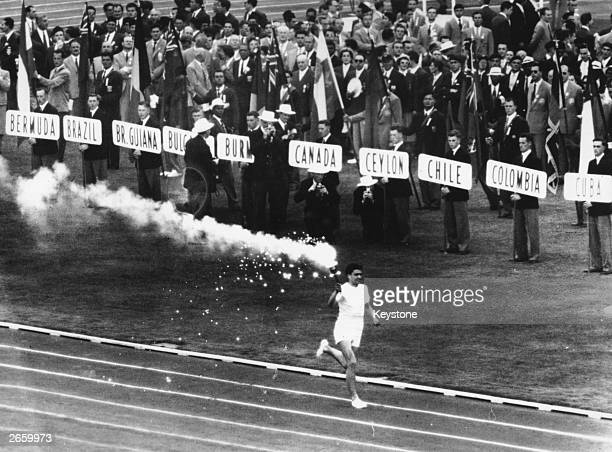 Australian athlete Ron Clarke holder of the junior mile record carries the Olympic torch into the stadium during the opening ceremony of the 1956...