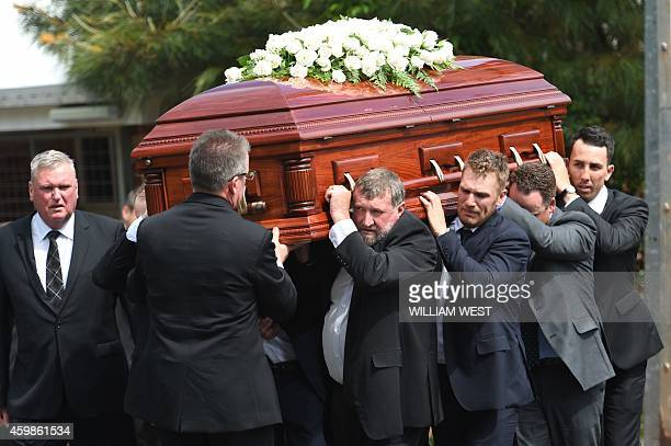 Australian batsman Aaron Finch carries the coffin of Australian batsman Phillip Hughes with other friends and family after his funeral in his home...
