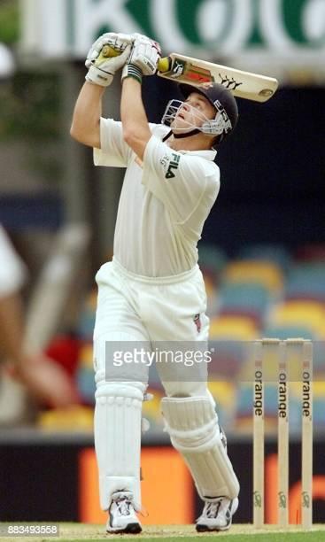 Australian batsman Adam Gilchrist lofts a ball high as he heads towards a century against New Zealand on the third day of the first Test Match being...