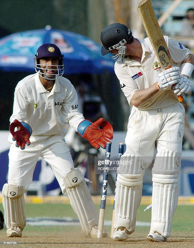 Australian batsman, Damien Martyn (R) is bowled out as Indian wicketkeeper Dinesh Kartik (L) looka on at the Wankhede Stadium, Bombay, 04 November 2004, on day two of the fourth Test between Australia and India. Australia, who shot India out for 104 in the first innings, were 99-3 in reply by tea on the second day of the fourth and final cricket Test . AFP PHOTO/Rob ELLIOTT