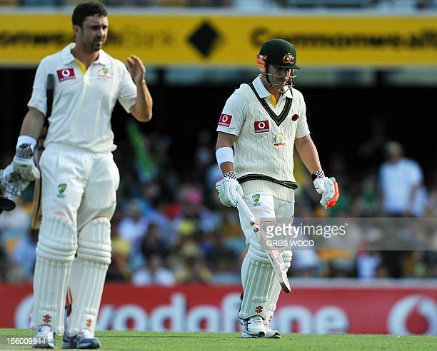 Australian batsman Dave Warner leaves the field past teammate Ed Cowan after being dismissed on day three of the first cricket Test between South...