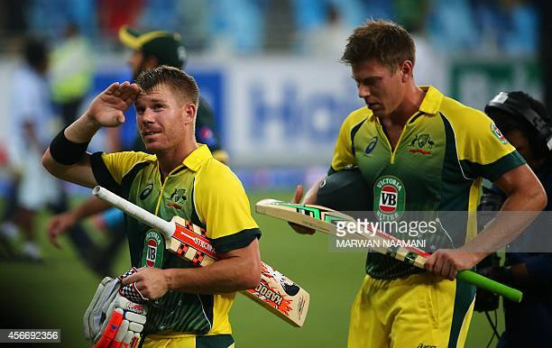 Australian batsman David Warner salutes the crowd as he and teammate James Faulkner leave the pitch at the end of the first International T20 cricket...