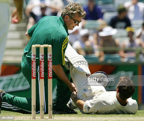 Australian batsman Justin Langer has his hamstring stretched by team physiotherapist Errol Alcott during the Test match against South Africa in Perth...