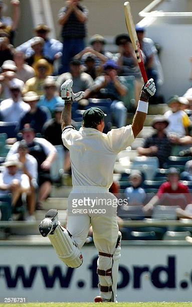 Australian batsman Matthew Hayden raises his arms in the air after scoring a triple century during the first Test against Zimbabwe at the WACA ground...