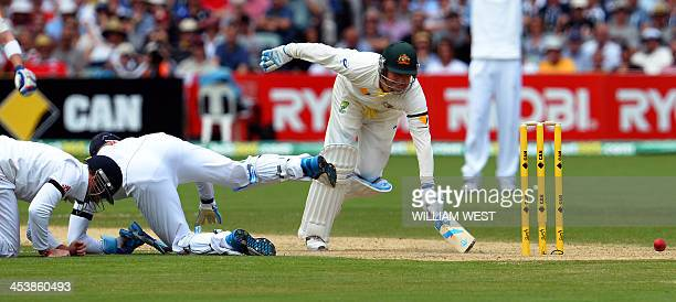 Australian batsman Michael Clarke dives as England players Ian Bell and Matt Prior attempt to run him out on day two of the second Ashes Test cricket...