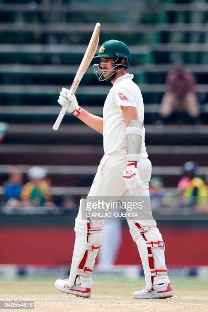 Australian batsman Pat Cummins raises his bat as he celebrates scoring half century on the third day of the fourth Test cricket match between South...