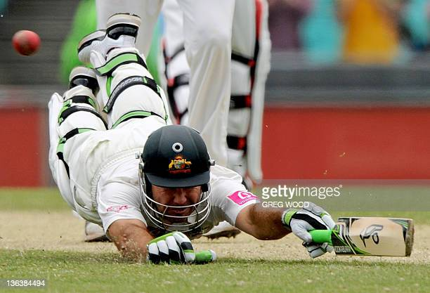 Australian batsman Ricky Ponting dives to make his ground and score a run to reach his 100 on day two of the second cricket Test against India at the...