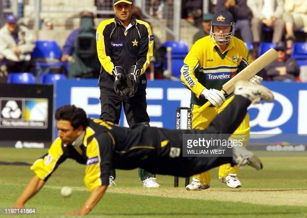 Australian batsman Steve Waugh drives a ball past the diving Saqlain Mushtaq as wicketkeeper Younis Khan looks on in their one-day match played at...