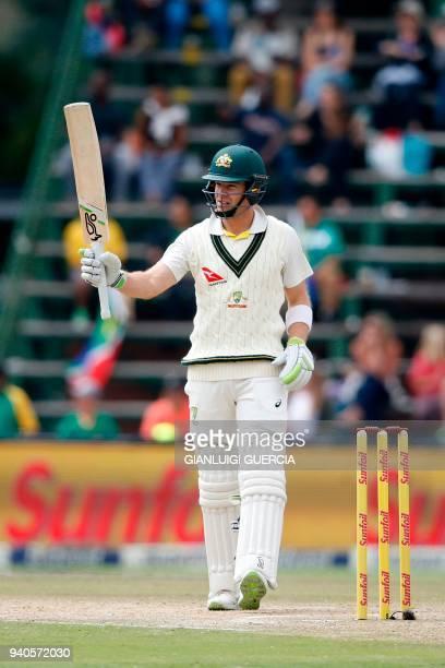 Australian batsman Tim Paine raises his bat as he celebrates scoring half century on the third day of the fourth Test cricket match between South...