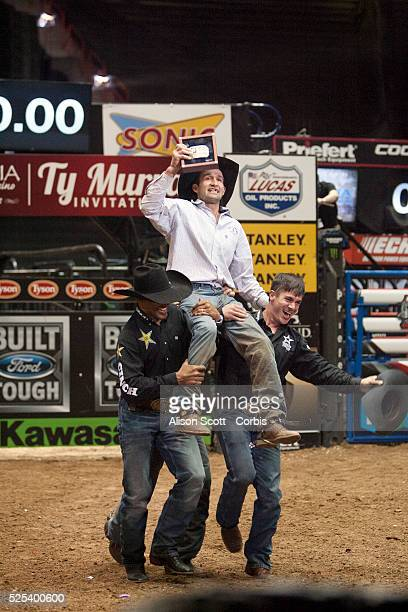 Australian Ben Jones celebrates by being carried on the shoulders of Valdiron de Oliveira and Mike Lee after winning his first Professional Bull...