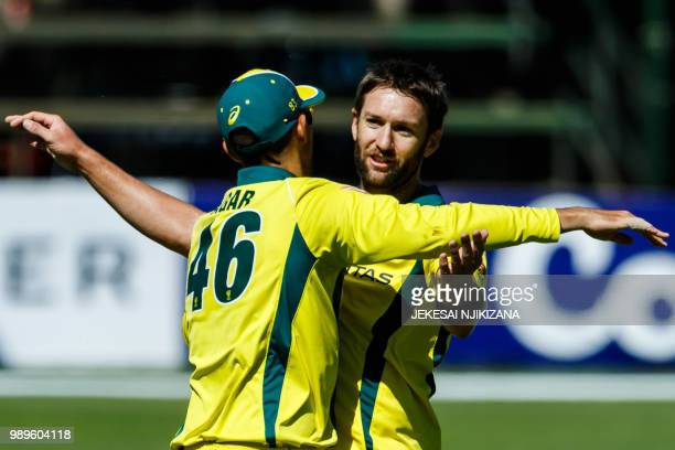 Australian bowler Andrew Tye celebrates a wicket with teammate Ashton Agar during the second match between Australia and Pakistan as part of a T20...