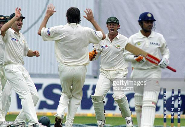 Australian bowler, Glenn McGrath jubilates along with teammates Simon Katich and Adam Gilchrist the wicket of Virender Sehwag for three runs as he...