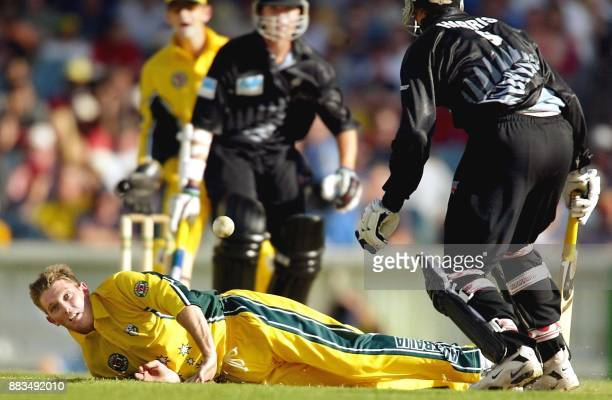 Australian bowler Ian Harvey dives to stop the ball as teammate Adam Gilchrist and New Zealand batsmen James Franklin and Chris Harris look on in...