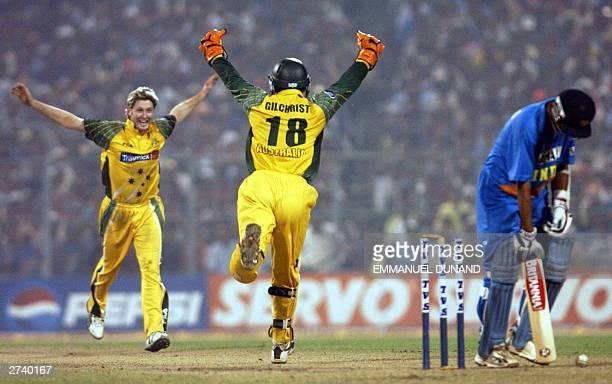 Australian bowler Michael Clarke celebrates with wicket keeper Adam Gilchrist after bowling out Indian batsman Rahul Dravid in the final of the...