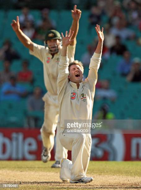 Australian bowler Michael Clarke with teammate Phil Jaques celebrate taking the wicket of RP Singh of India on the final day of the second Test match...
