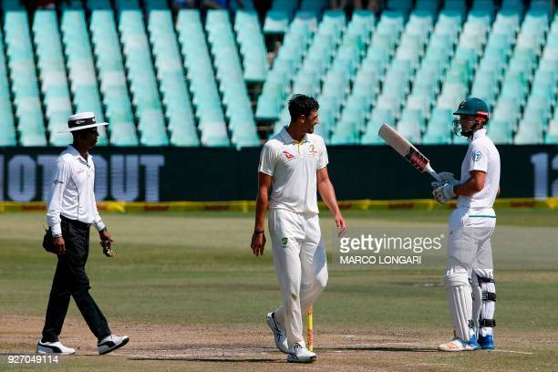Australian bowler Mitchell Starc is watched by umpire Kumar Dharmasena as he speaks with South African batsman Theunis de Bruyn during the fourth day...