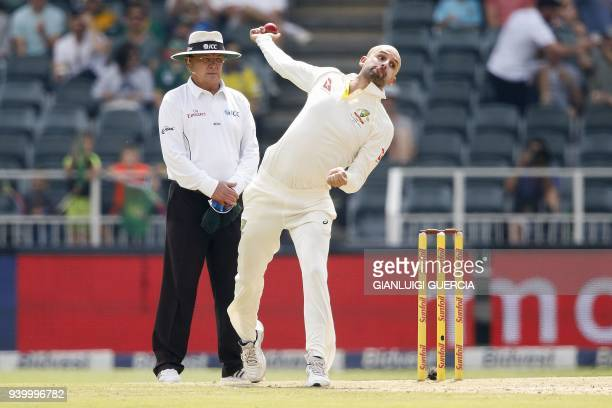 Australian bowler Nathan Lyon bowls on South African batsman Dean Elgar during the first day of the fourth cricket Test match between South Africa...