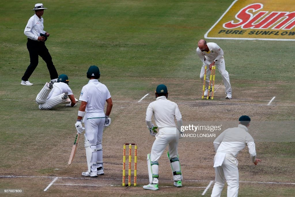 Australian bowler Nathan Lyon (TOP) breaks the stumps to run out South African batsman AB de Villiers (2L) during the fourth day of the first Test cricket match between South Africa and Australia at The Kingsmead Stadium in Durban on March 4, 2018. /