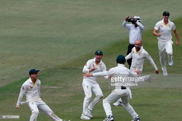 Australian bowler Nathan Lyon celebrates with teammates after taking a throw from David Warner to run out unseen South African batsman AB de Villiers...